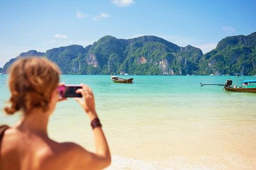 Mujer fotografiando una playa