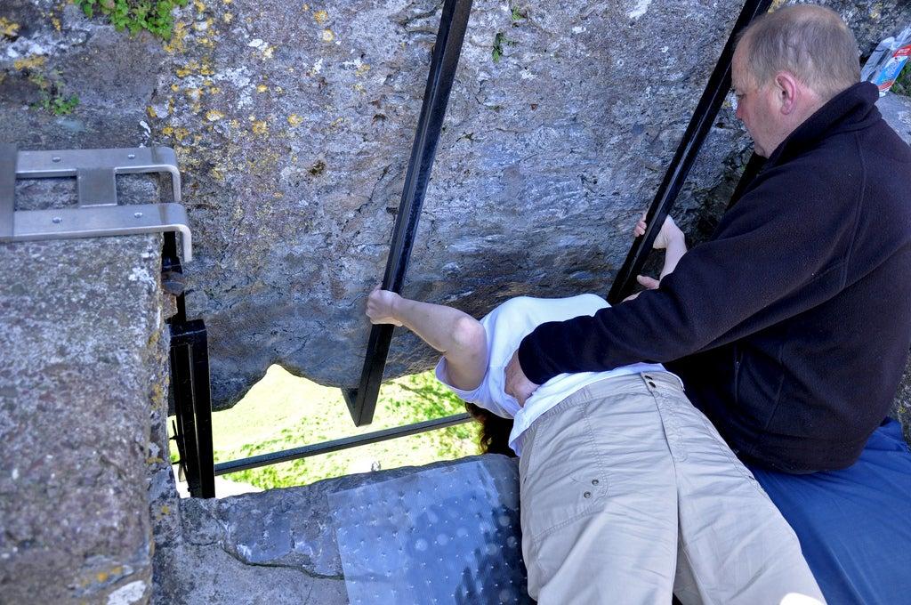 Mujer apunto de pedir un deseo en el castillo de Blarney