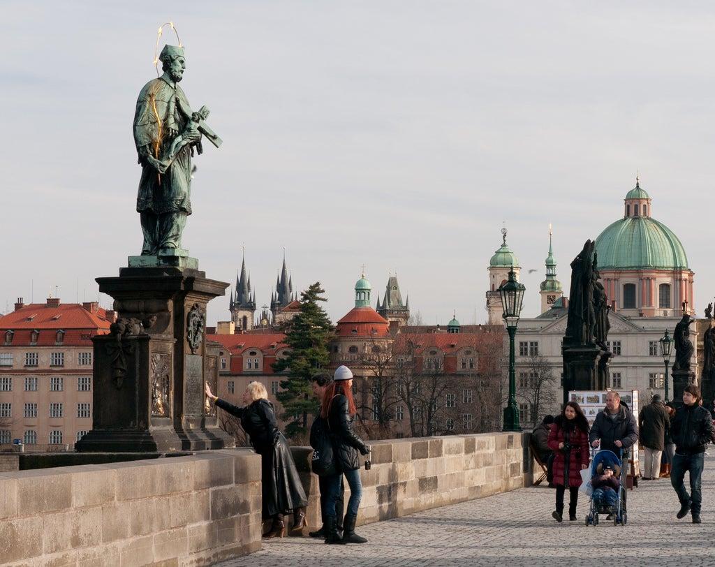 Mujer pidiendo un deseo en la estatua de San Juan Nemopuceno de Praga