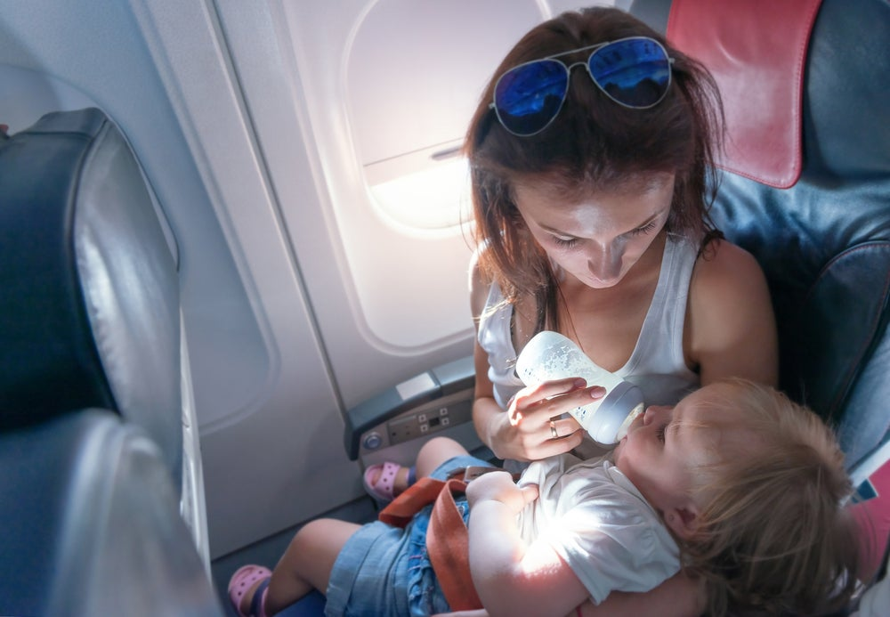 Madre dando de comer a su hijo en el avión