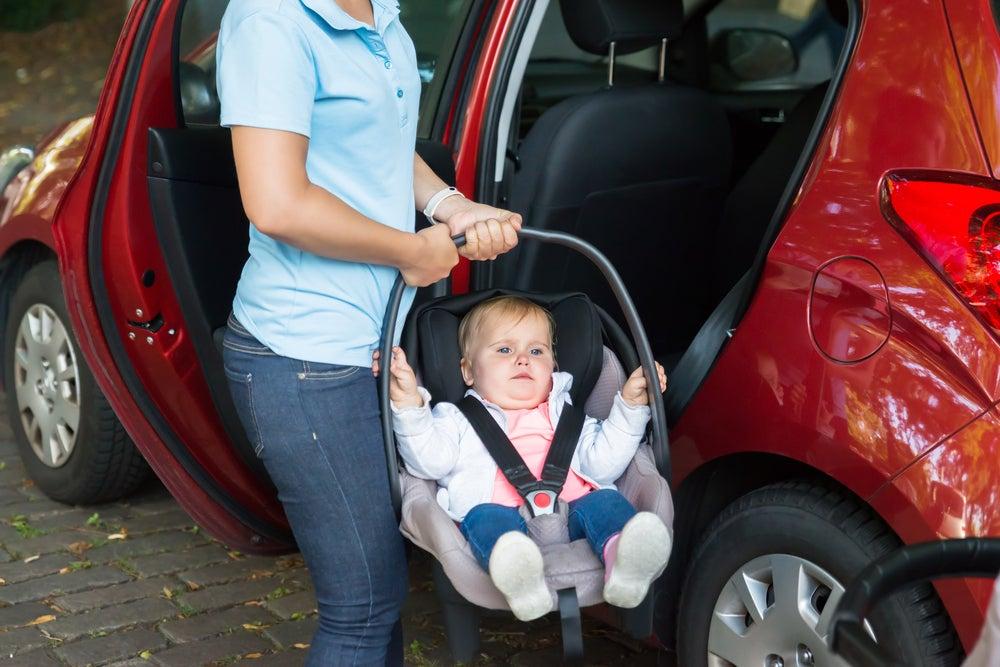 MAdre sacando a su bebé del coche