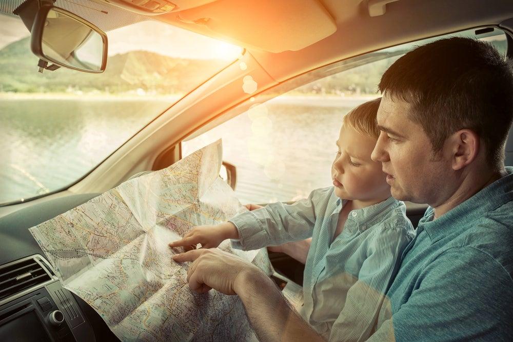 Padre en el coche que va a hacer un viaje con niños