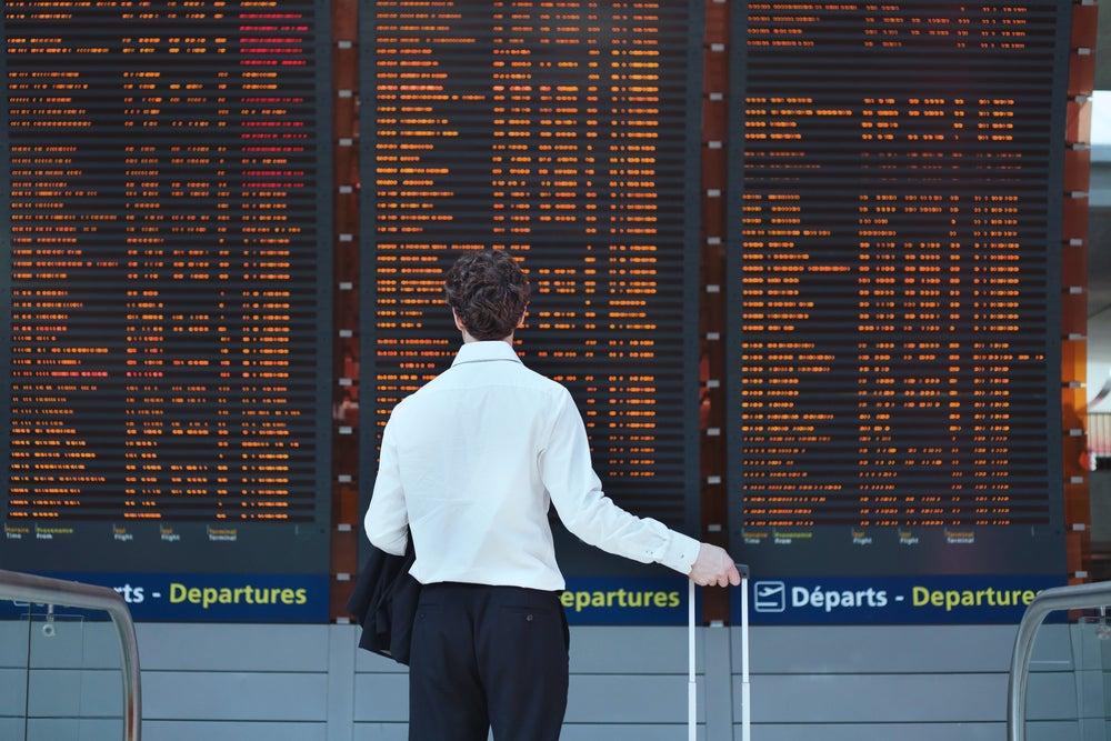 Hombre en el aeropuerto mirando un cartel