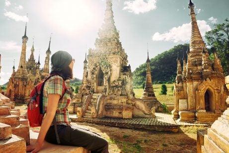 Mujer que sabe viajar con poco dinero en un templo asiático