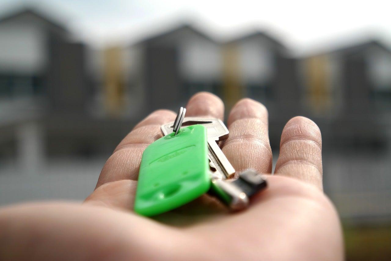 Hombre dando una llave, símbolo de economía colaborativa