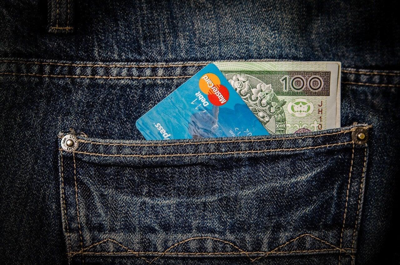 Hombre con dinero y tarjetas en el bolsillo