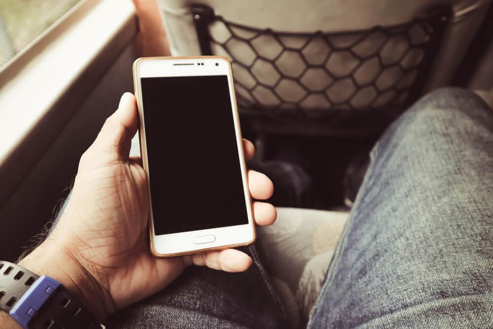 Hombre con un móvil en el autobús