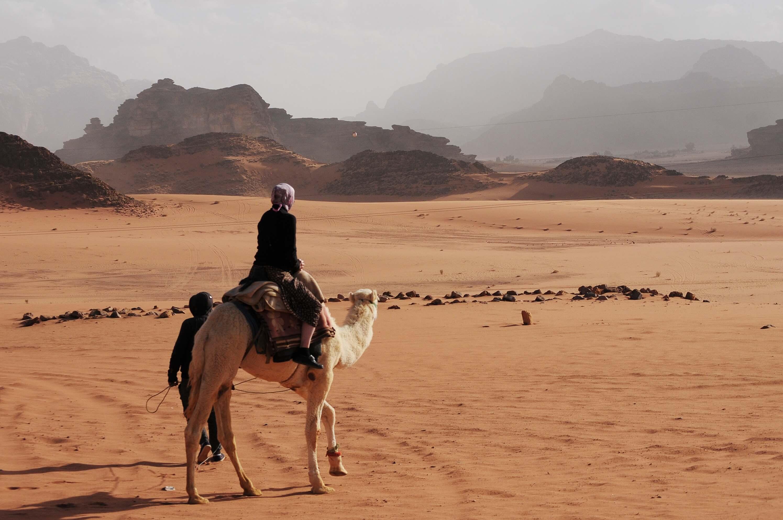 Mujer a camello por Wadi Rum