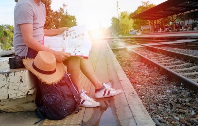 Chico con mapa en una vía de tren