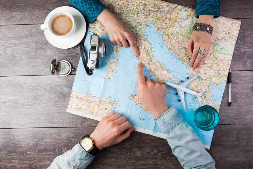 Pareja planeando el viaje de novios sobre un mapa