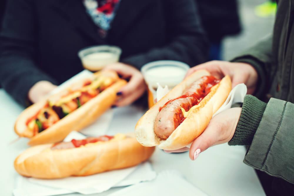 Gente comiendo perritos calientes