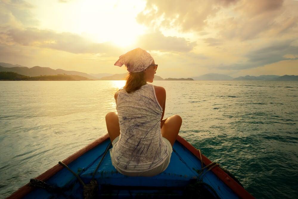 Mujer mirando el atardecer en una barca