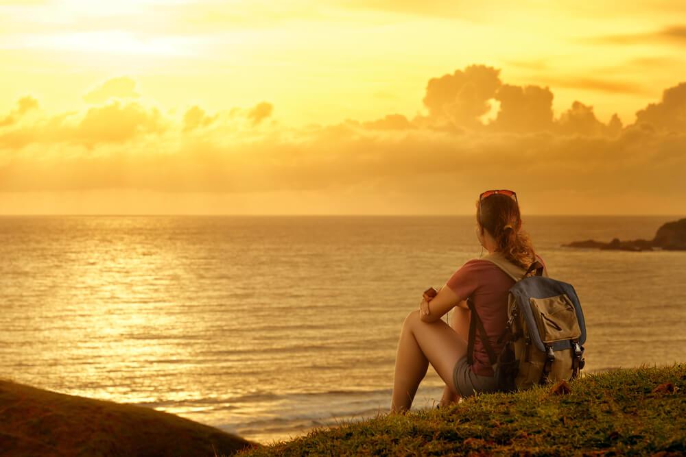 Chica mirando el paisaje al atardecer