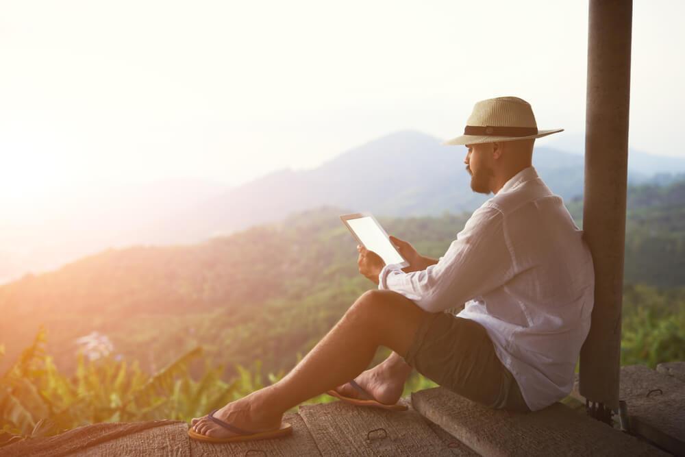 Hombre sentado con uno de los mejores libros para viajar en la mano