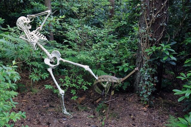 Escultura de un esqueleto atrapado en una trampa
