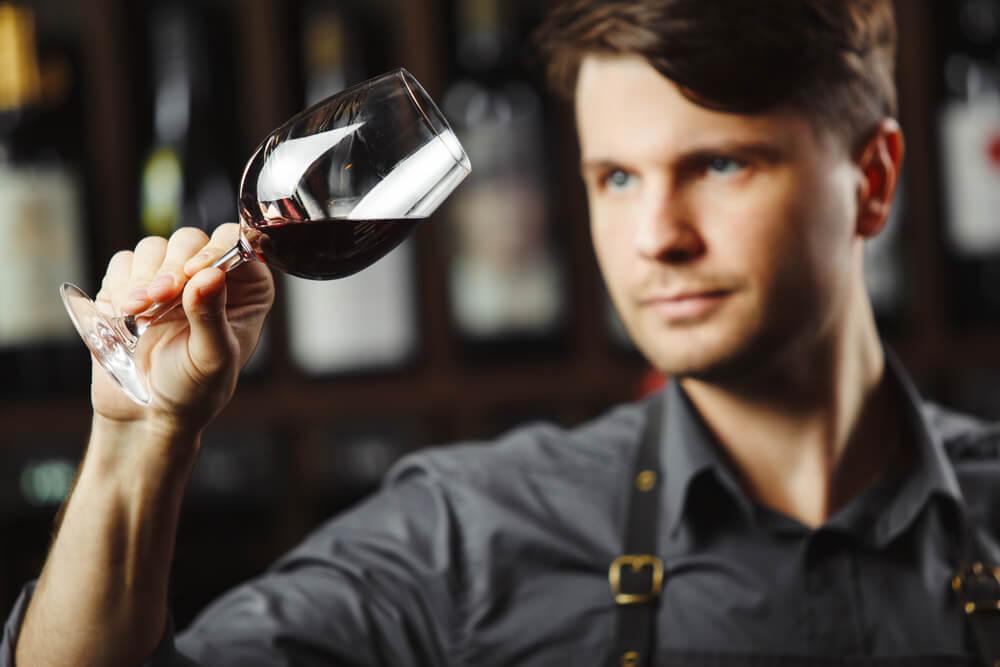 Hombre mirando una copa de vino