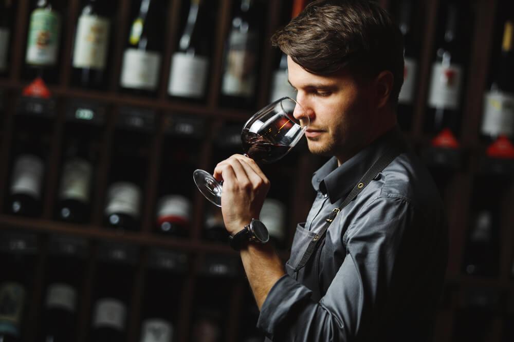 Hombre oliendo una copa de vino