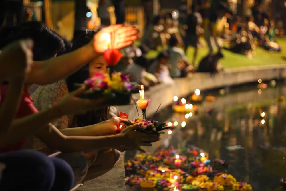 Genta lanzando al agua luces en el Festival Loi Kratong