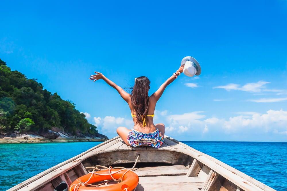 Joven que hace un viaje en solitario feliz en una canoa