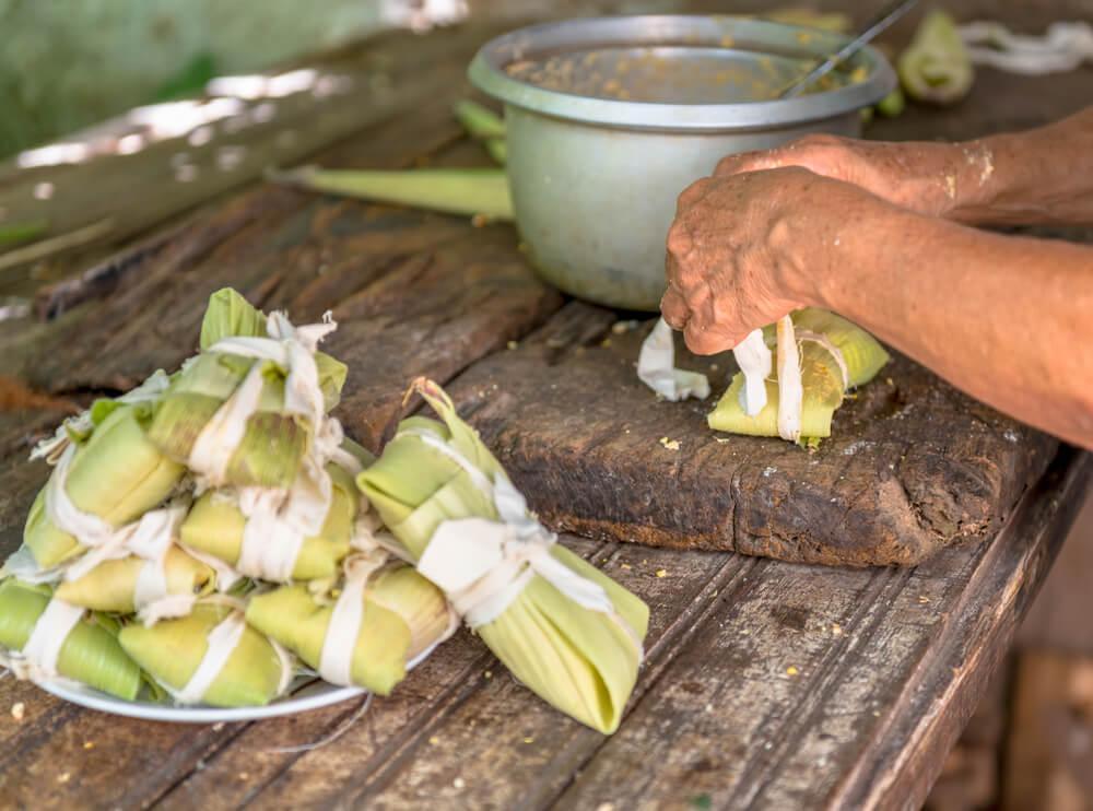 Mujer preparando tamales típicos de la comida cubana