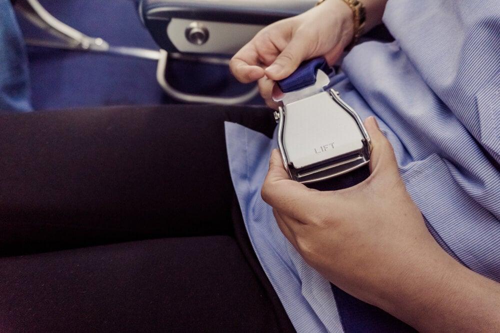 Motivos para expulsarte de un avió: mujer quitándose el cinturón