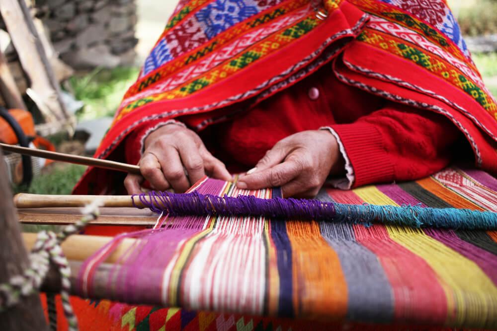 Artesanías de Perú: mujer hilando con lana de alpaca
