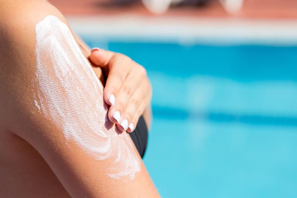 Mujer extendiéndose crema protectora