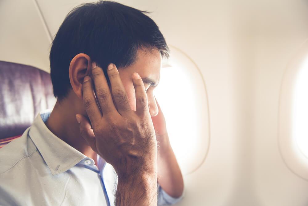 Pasajero con dolor de oídos, uno de los uno de los malestares que pueden surgir en un avión