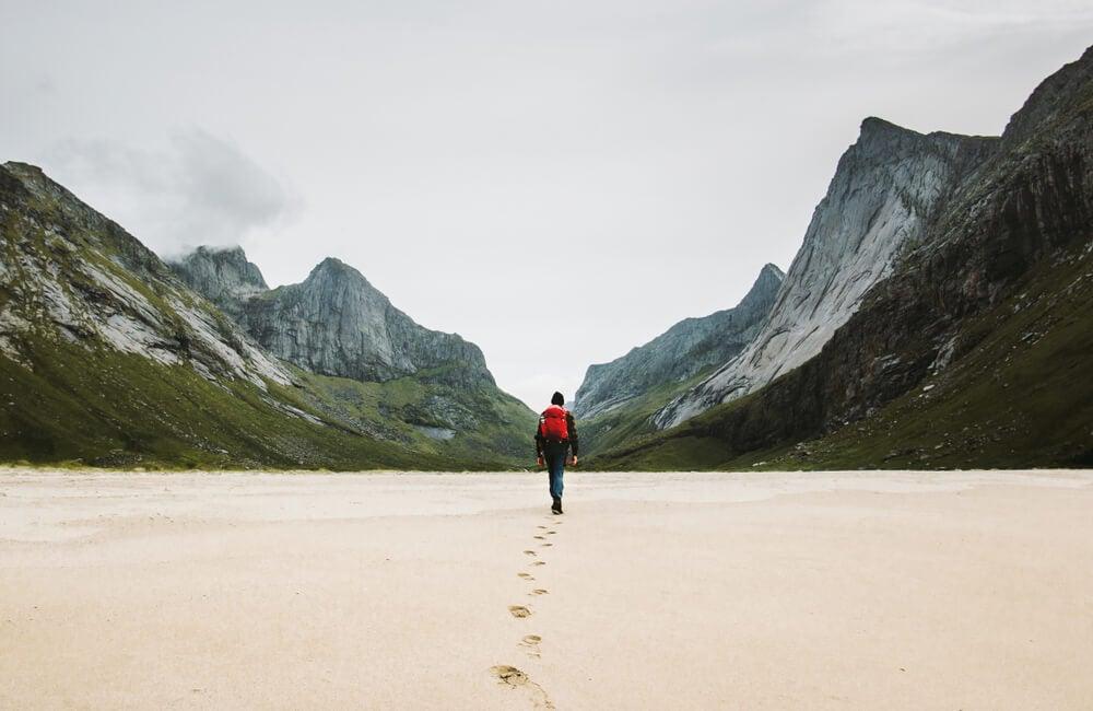 Viajero caminando entre montañas para desestresarse, otra razón de por qué viajamos