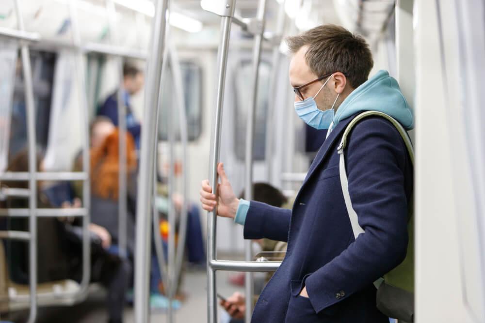 Hombre con mascarilla para protegerse de coronavirus en el transporte público