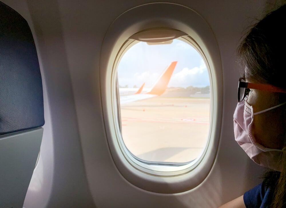 Mujer en avión con mascarilla