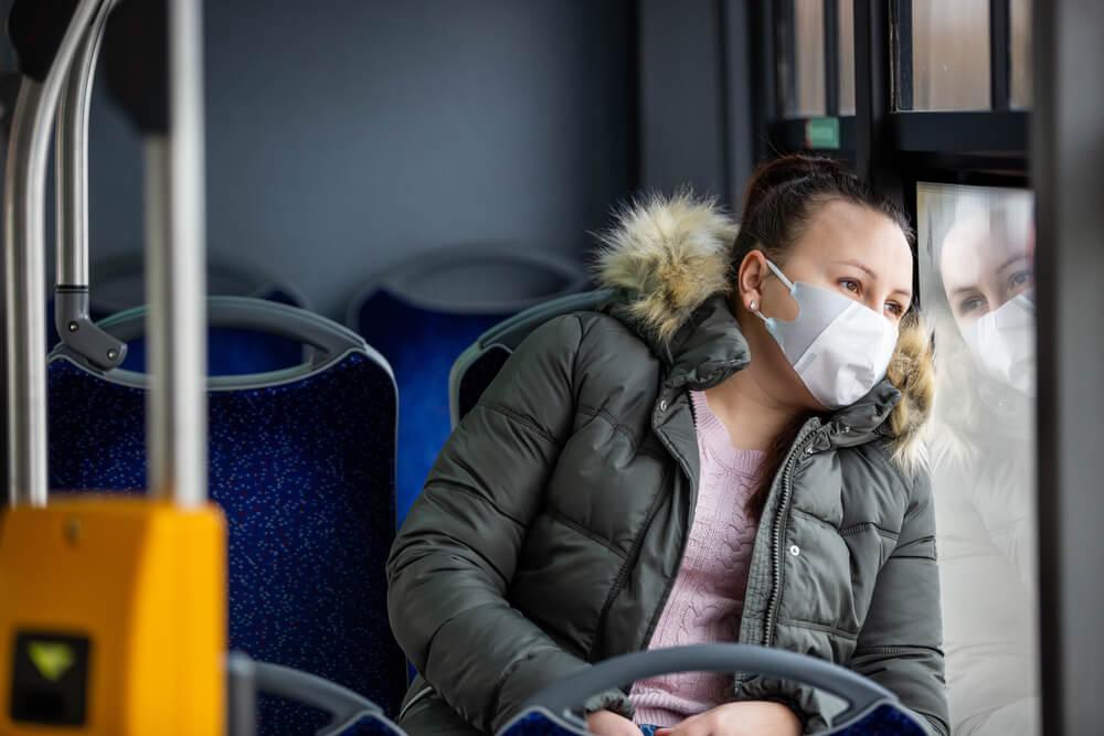 Mujer en bus con mascarilla