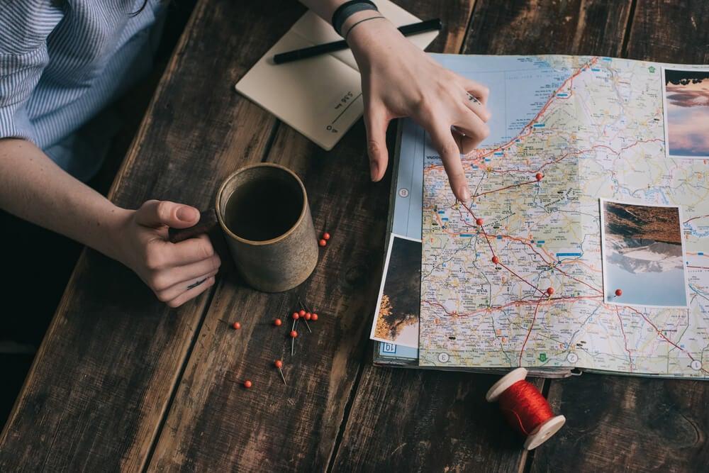 Mujer marcando una ruta en un mapa