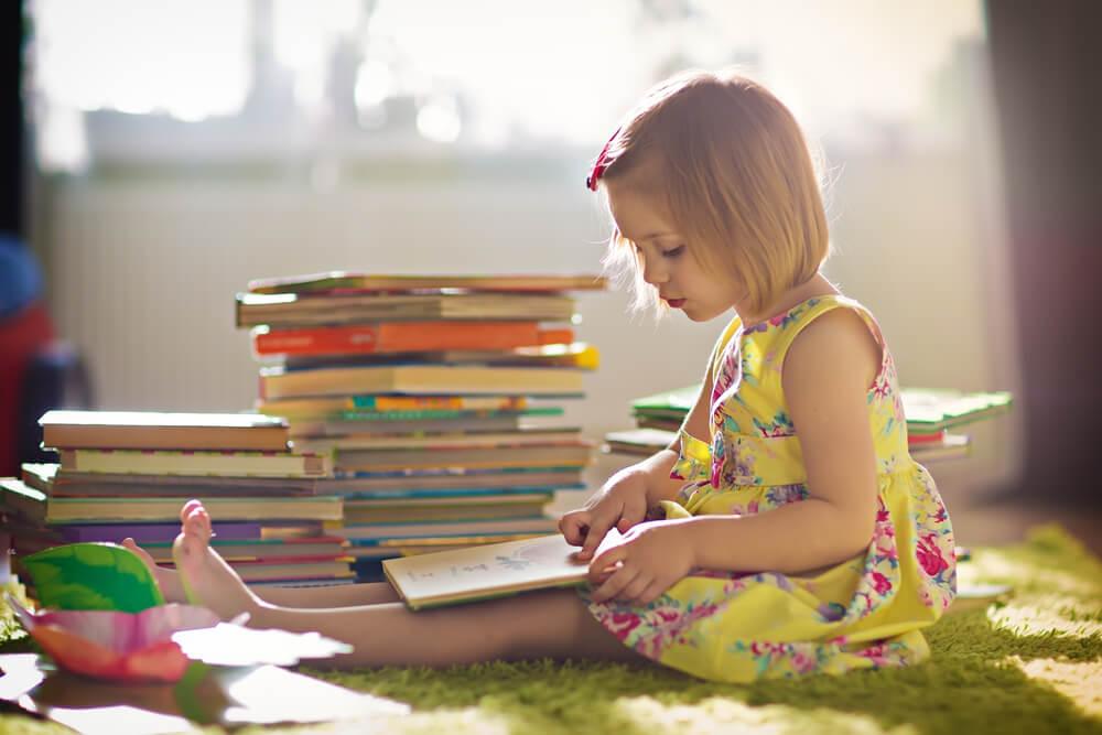 Niña leyendo en casa durante Día del Libro por el confinamiento.
