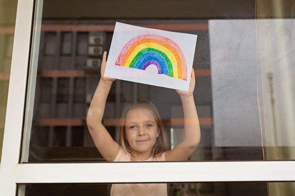 Niña muestra un arcoiris a través de su ventana.