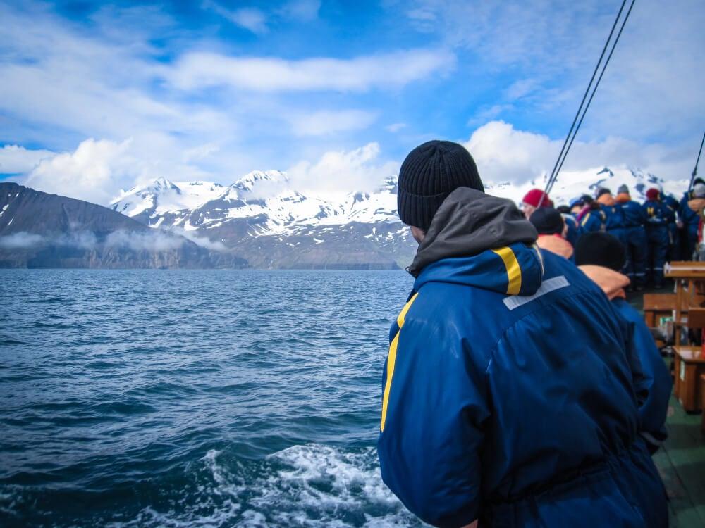 Personas en un barco para ver ballenas en Islandia.