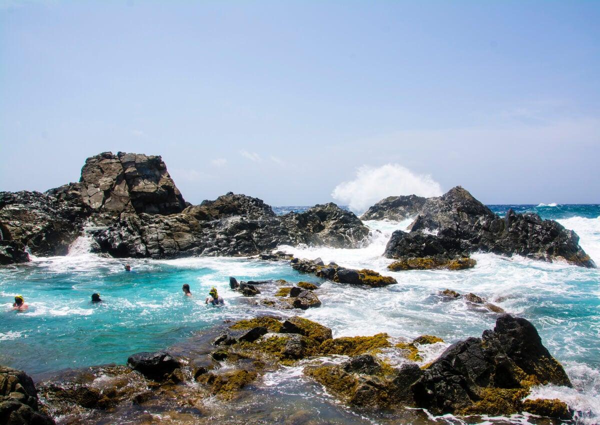 Turistas disfrutando de las piscinas naturales en Aruba.