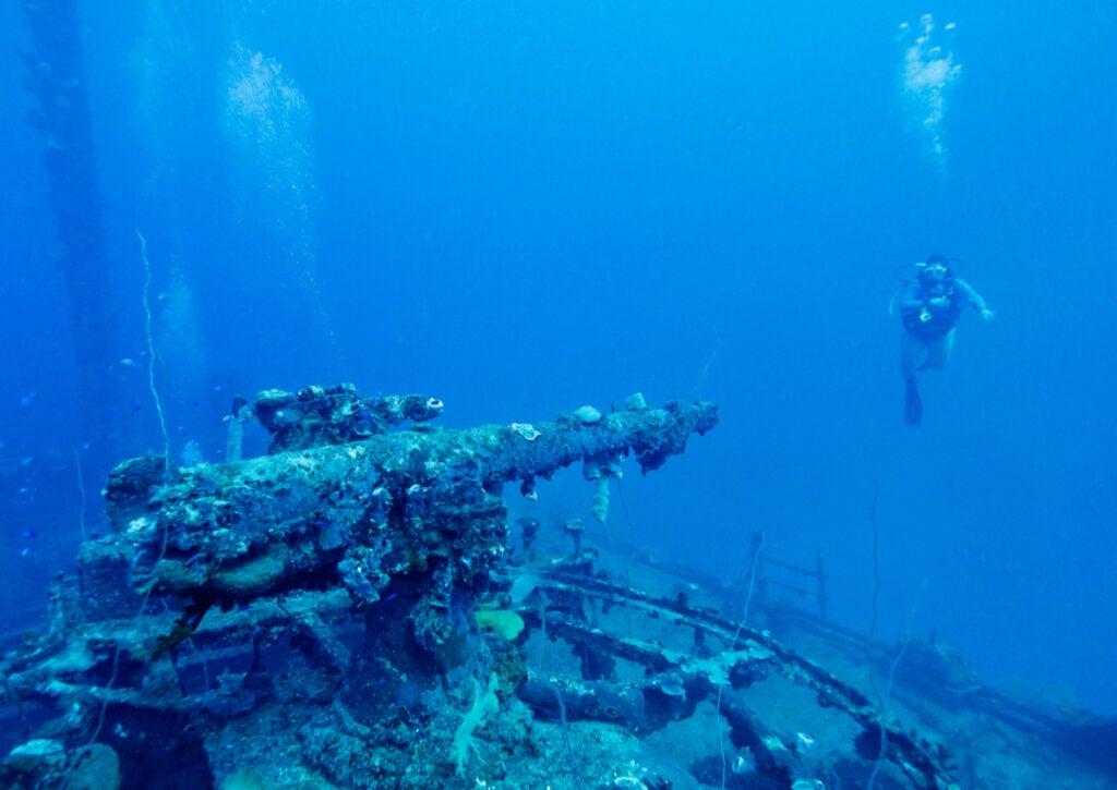 Turista buceando en el atolón Truk, cerca de una ametralladora hundida.