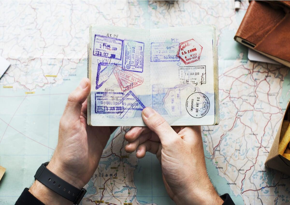 Un pasaporte lleno de sellos en manos de un viajero.