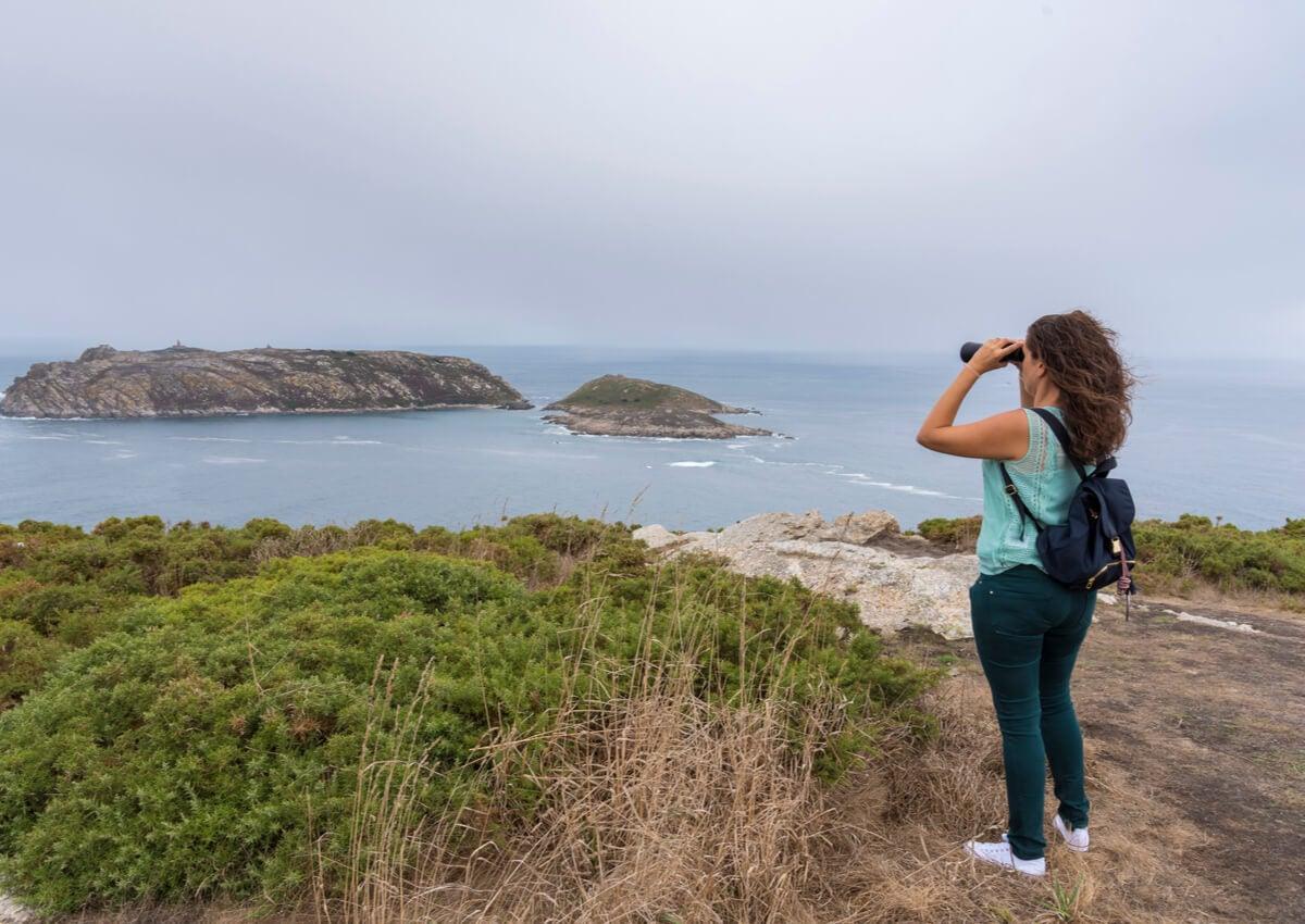 Chica observa con binoculares en las islas Sisargas.