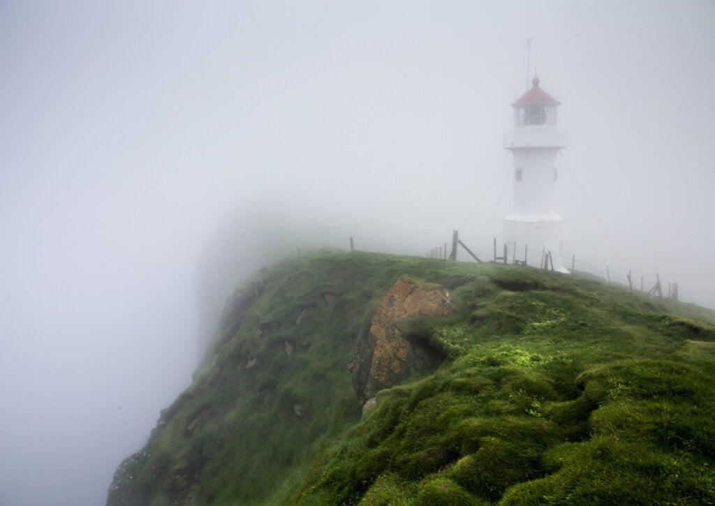 Faro en la costa de una isla con niebla.