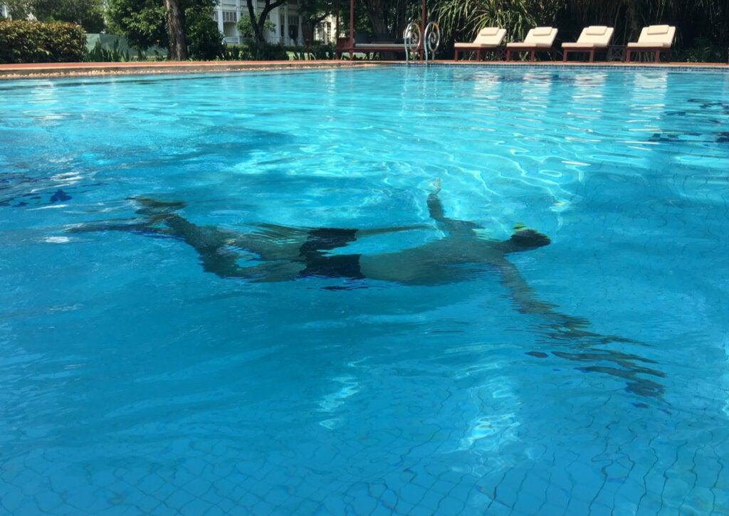 Turista haciendo natación en la piscina de un hotel.