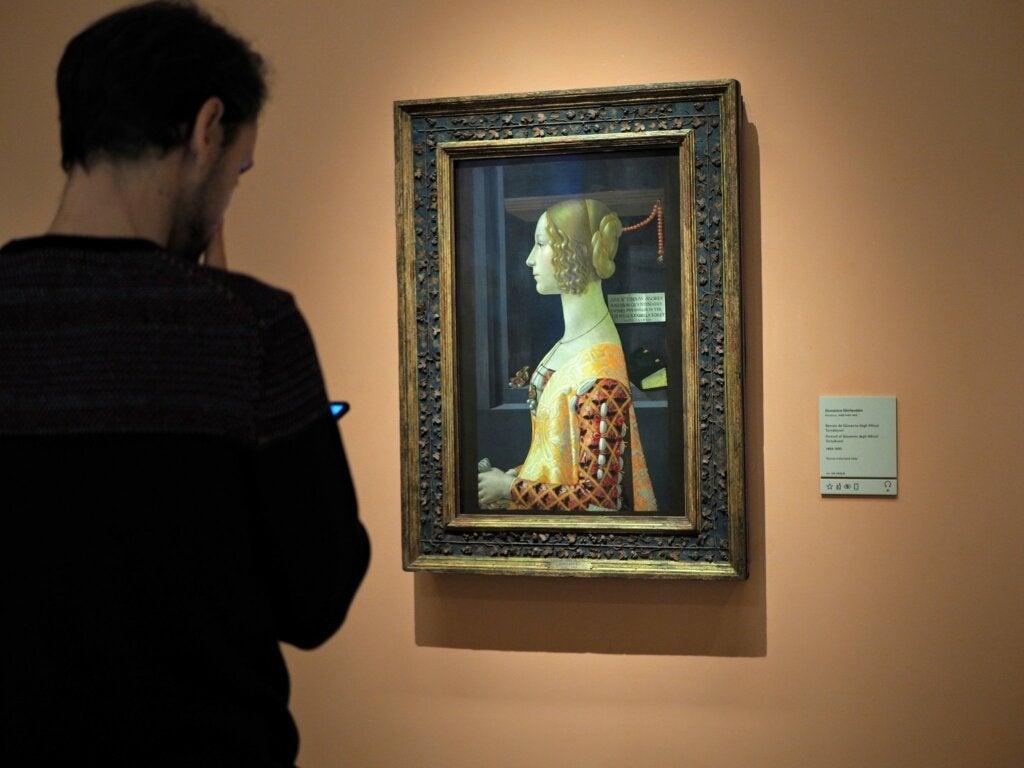 Turista observando el retrato de Giovanna Tornabuoni.