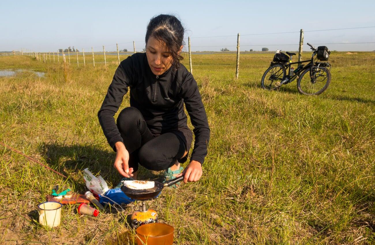 Mujer haciendo cicloturismo y preparando su propia comida.