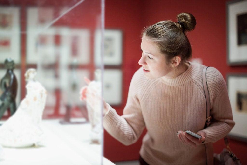 Mujer viendo obra de arte en un museo.
