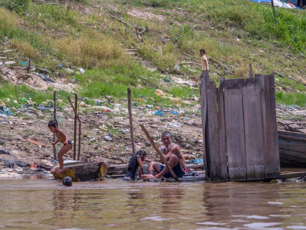 Indígenas tomando un baño a la costa del río.